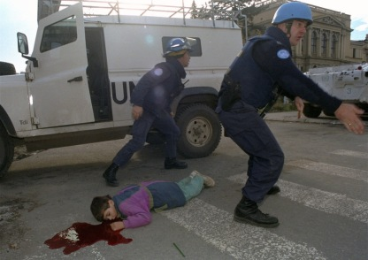 Seven-year-old Bosniak child, Nermin Divovic, lies mortally wounded in a pool of blood as unidentified American and British U.N. firefighters arrive to assist after he was shot in the head by Serbian snipers in Sarajevo Friday, November 18, 1994. The U.N. firefighters were at his side almost immediately, but the boy died outright. Serbs terrorized Sarajevo civilians and killed at least 1500 children in the besieged Bosnian capital. (Photographer: Enric Marti)